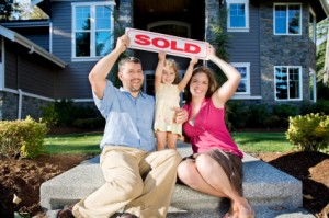 Excited family with SOLD sign